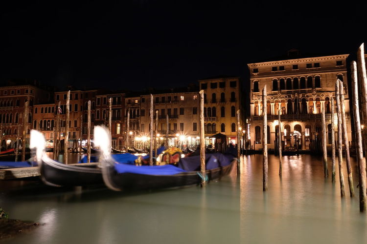 Boats moored in illuminated canal by buildings in city at night