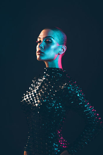 Young woman with shaved head against black background
