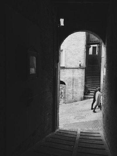 People walking on street seen through archway
