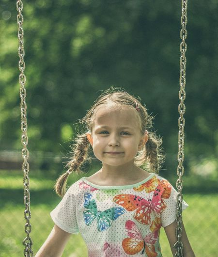 Portrait of girl sitting on swing at park