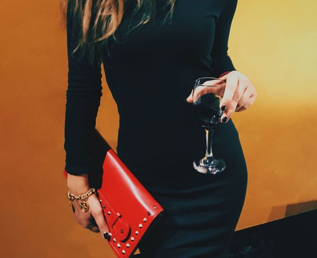Midsection of woman holding wineglass and purse while standing against wall