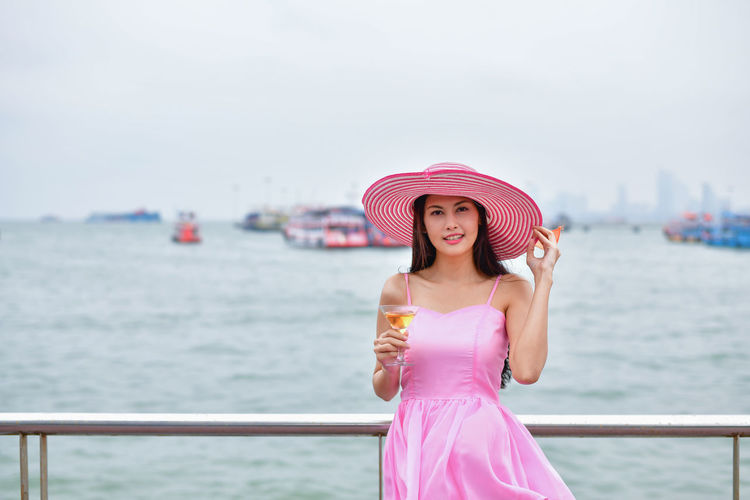 Portrait Of Mid Adult Woman Holding Drink While Standing By Sea Against Sky