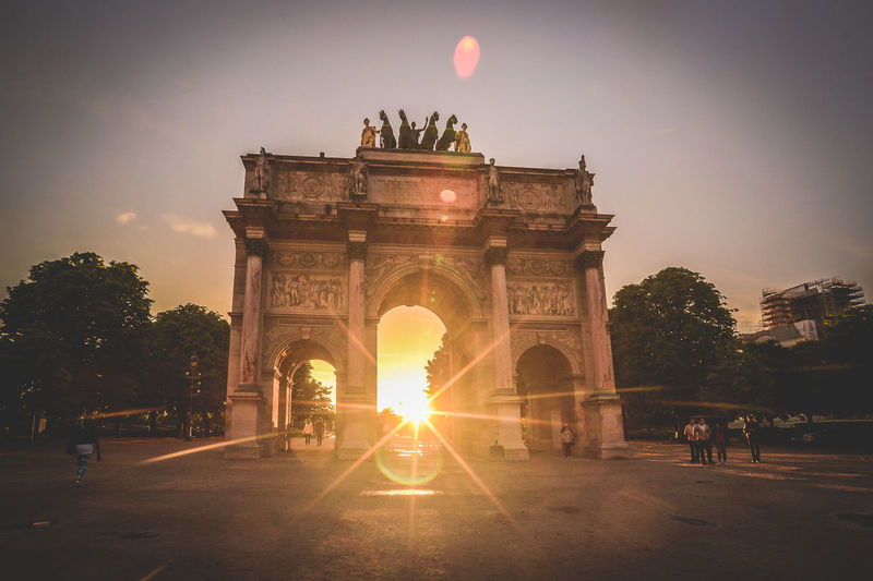 Triumphal arch in city during sunset
