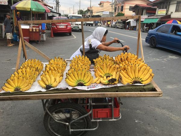A woman, selling bananas, pushes her tricycle cart along a national highway in Kawit, Cavite, just 21 kilometers (13 miles) south of the Philippine capital Manila. Transportation Tricycle CyclingUnites Cycling Vendors On Wheels Banana Bananas For Sale Bananas EyeEmBestPics EyeEm Best Shots Streetphotography Street Photography Philippines Cavite Food Stories