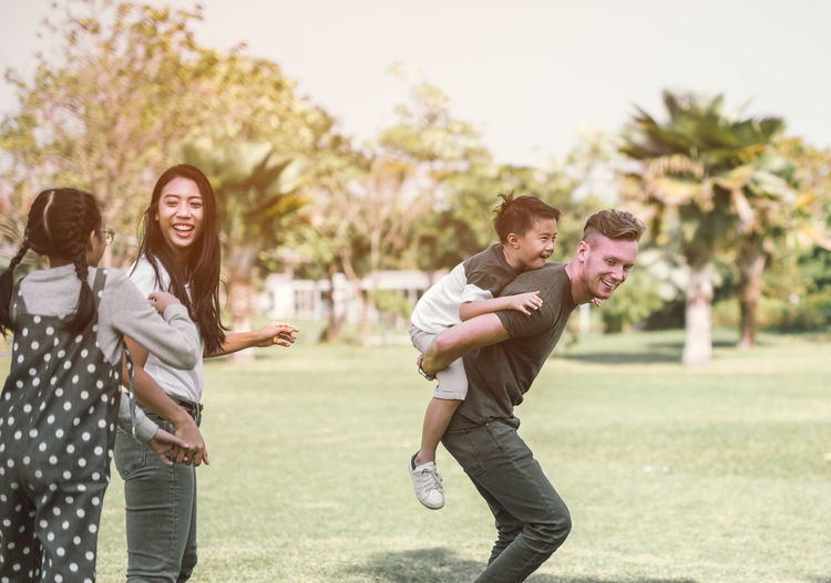 Dad and son having fun outdoors.concept of a happy family. Asian  Camping Family Fun Happiness Happy Holiday Love Nature Picnic Piggyback Vacations Boy Carry Daughter Family Time Outdoors Parent Park Ride Smile Smiling Son Teen Togetherness