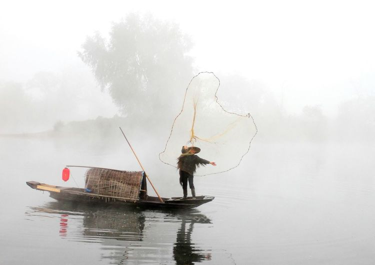 Man standing on boat while fishing in lake against sky