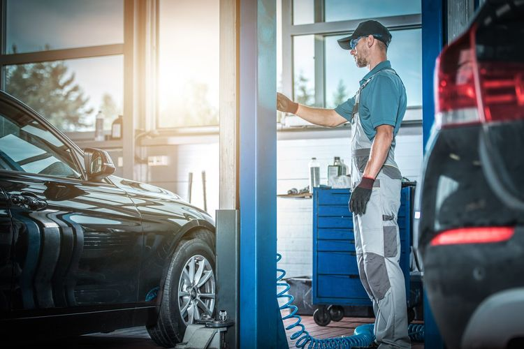 Side view of mechanic standing at garage