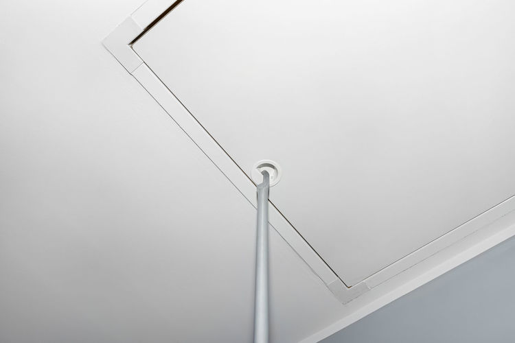 Low angle view of cables against white wall