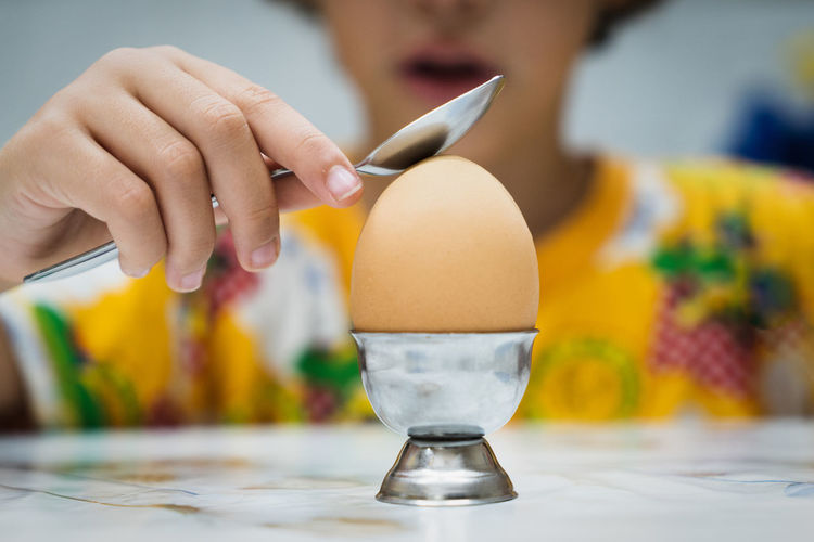Close-up of boy with egg on table