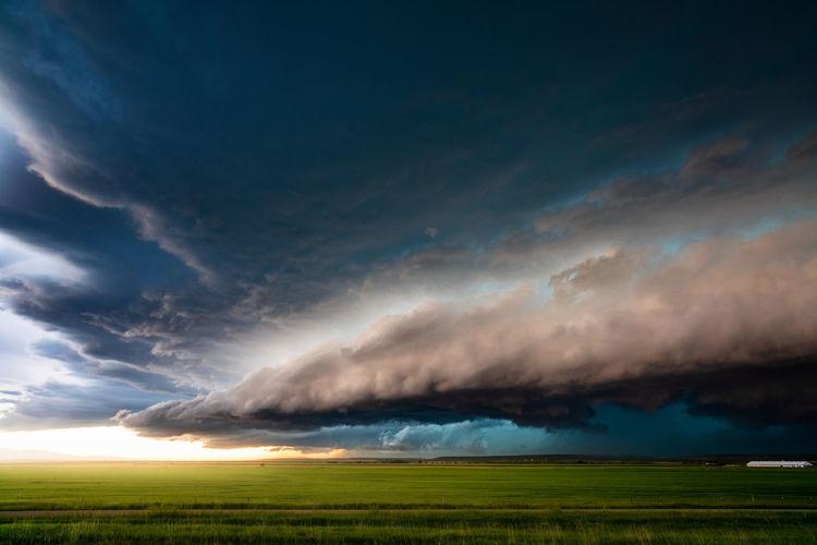 Sunlight illuminates dramatic storm clouds ahead of a thunderstorm near lewistown, montana.