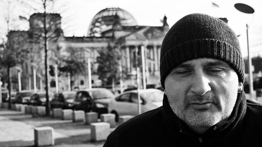 Close-up portrait of man against reichstag building