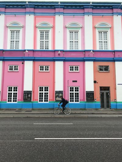 Man riding bicycle on road against pink building