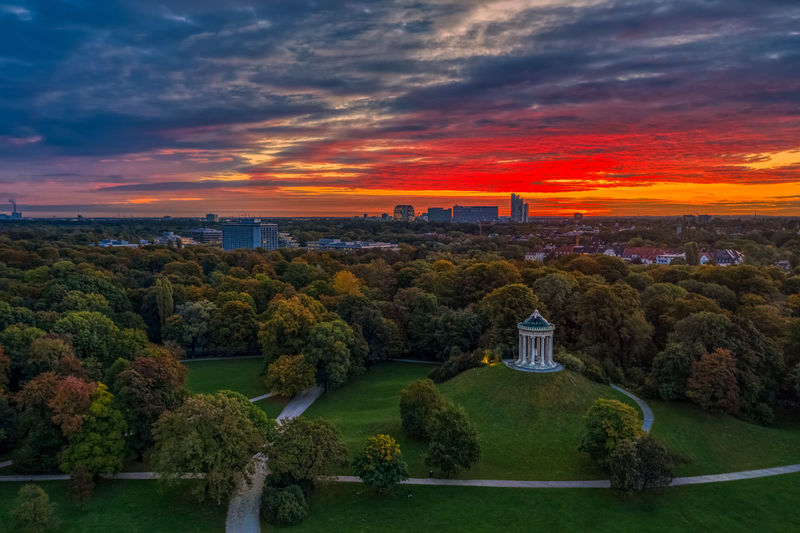 Scenic view of trees and buildings against sky during sunset