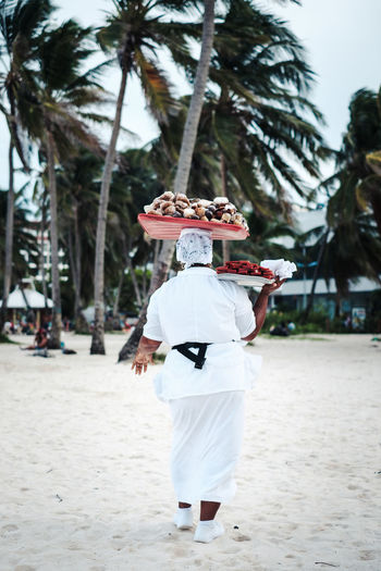 Rear View Of Female Vendor Selling Food At Beach