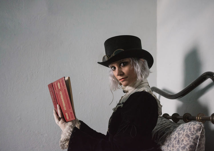 Side view portrait of woman wearing costume while reading book on bed at home