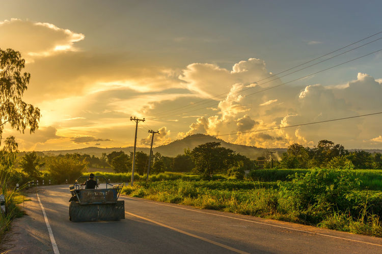 Tractor on road against cloudy sky during sunset