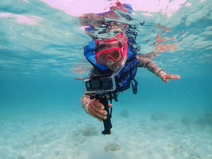 Man filming while swimming in sea
