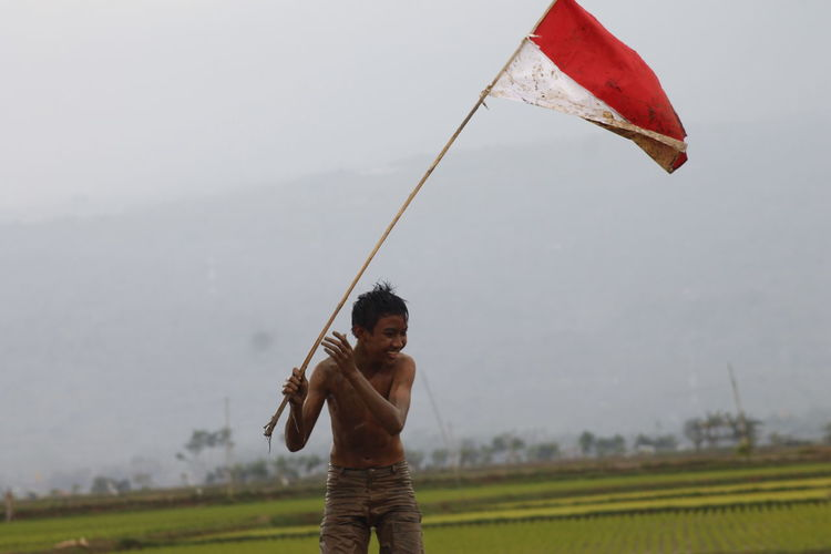 Shirtless boy holding flag while standing at farm against cloudy sky