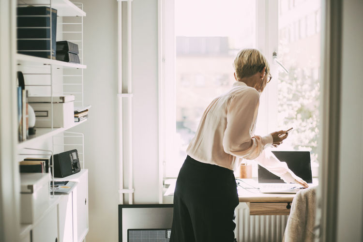 Woman standing by window at home