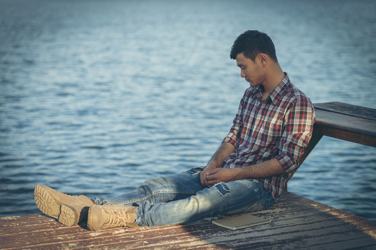 Young man sitting on pier over lake