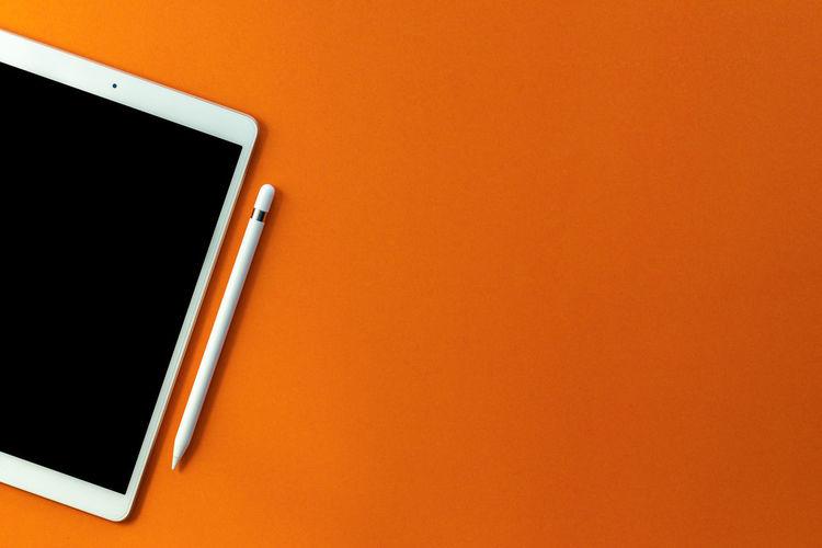 Close-up of smart phone against orange background