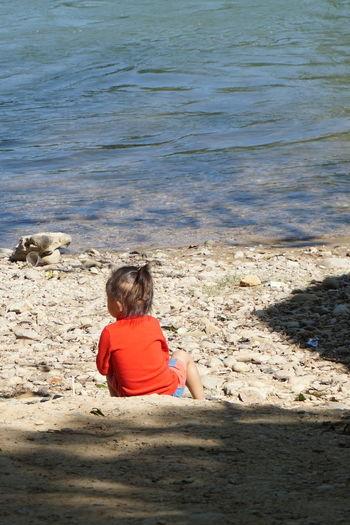 Girl sitting at sea shore