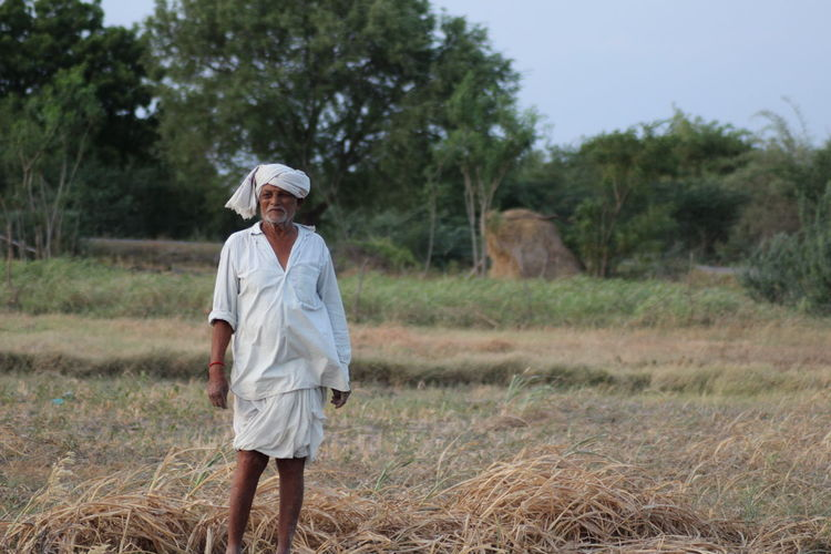 Farmer standing on field at farm