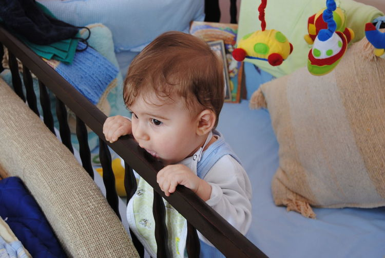 High Angle View Of Cute Baby Boy Standing In Crib At Home