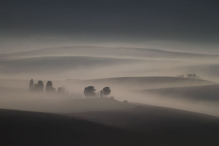 Silhouette landscape against sky during foggy weather