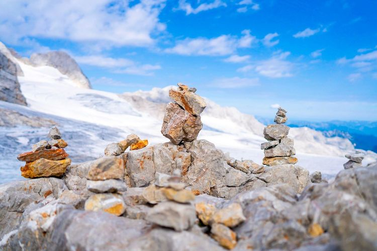 Stack of stones on rocks at mountain against sky
