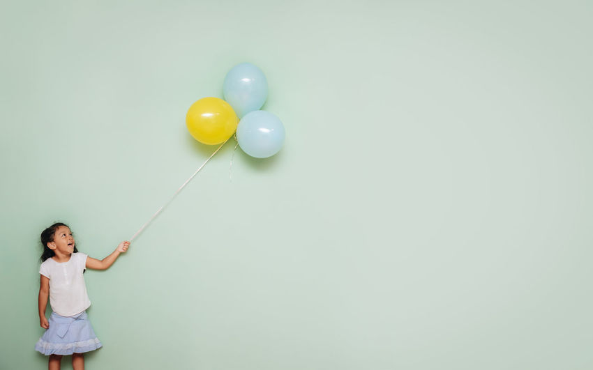 Girl  holding a bunch of colorful balloons against a blank teal wall