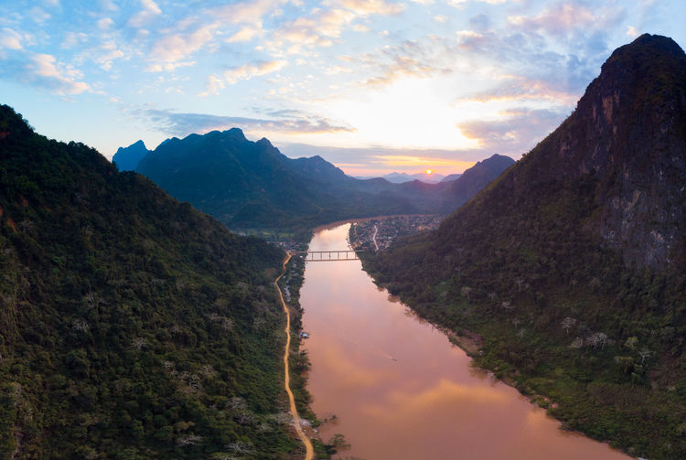 Scenic view of river amidst mountains against sky during sunset