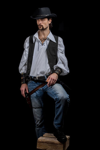 Handsome young man. This is an American cowboy. A vow to a white shirt, brown waistcoat and blue jeans. Black shoes on the feet. Carries a shtyapa, on a belt two pistols. The hair is of medium length; on the face is a beard and mustache. Authentic photo. Culture of America. Cowboy Wild West America American Gun National Authentic Moments Lifestyle One Person Candid Authentic Hat Clothing Casual Clothing Black Background Front View Full Length Standing Holding Three Quarter Length Men Young Adult Young Men Fashion Jeans