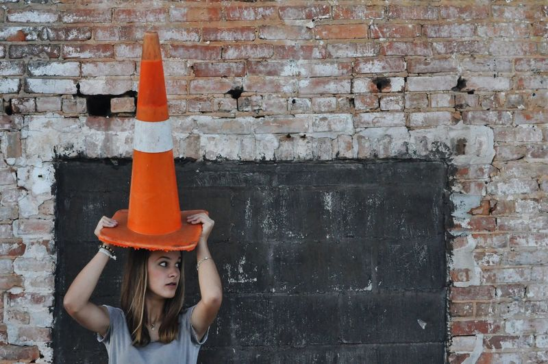 Woman holding traffic cone on head while standing against wall