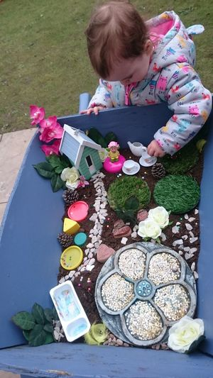 Child High Angle View Aerial View Children Only Flower One Person People One Girl Only Outdoors Day Babyhood 3XSPUnity 3XSPhotographyUnity Uniqueness, EyeEm Best Shots Fairy Garden Fairy Door Fairytales & Dreams Wheelbarrow Imagination Creative Different Textures Tea Party Natural Materials Garden Photography