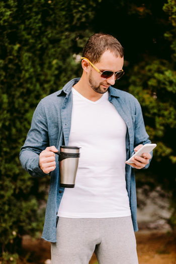 Man holding coffee cup looking away while standing against plant
