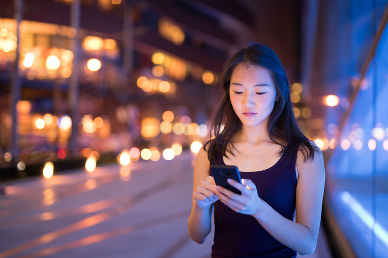 Young woman using phone while standing in illuminated city at night
