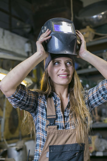 Smiling woman wearing helmet while standing in factory