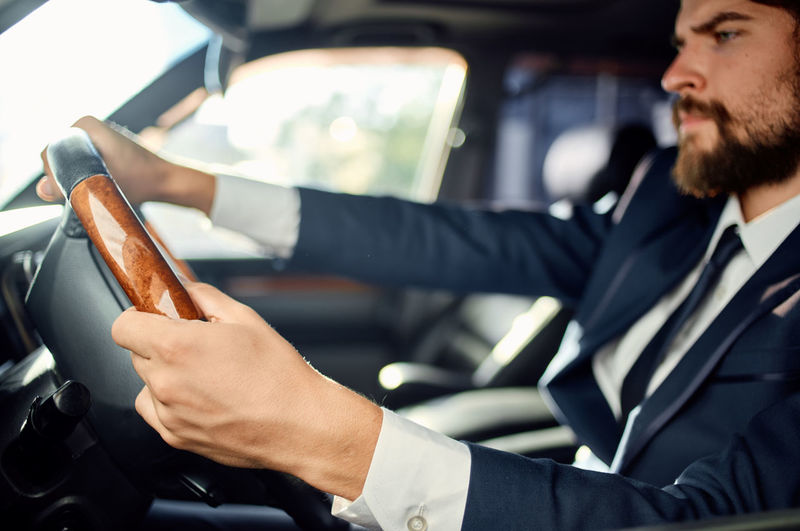 Midsection of man holding ice cream in car