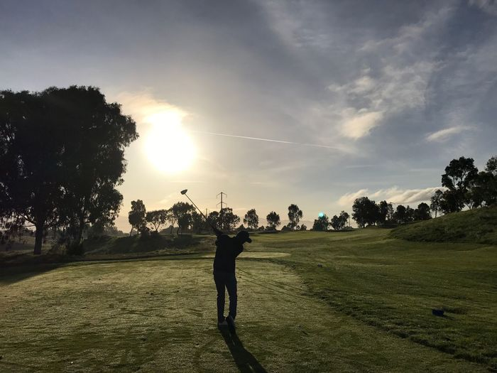 Silhouette man playing golf against sky