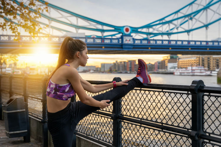 Athletic woman does her stretches after a early morning workout during sunrise in the city Architecture Connection Bridge City River Lifestyles One Person Sunset Leisure Activity Water Sky Real People Railing Cityscape Young Adult Focus On Foreground Sports Sunrise Urban City London Stretching Exercising Workout Woman Athlete Athletic Attractive Fitness