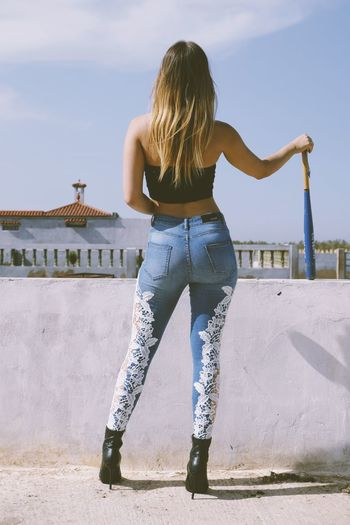 A sexy girl wearing jeans with a baseball bat at han