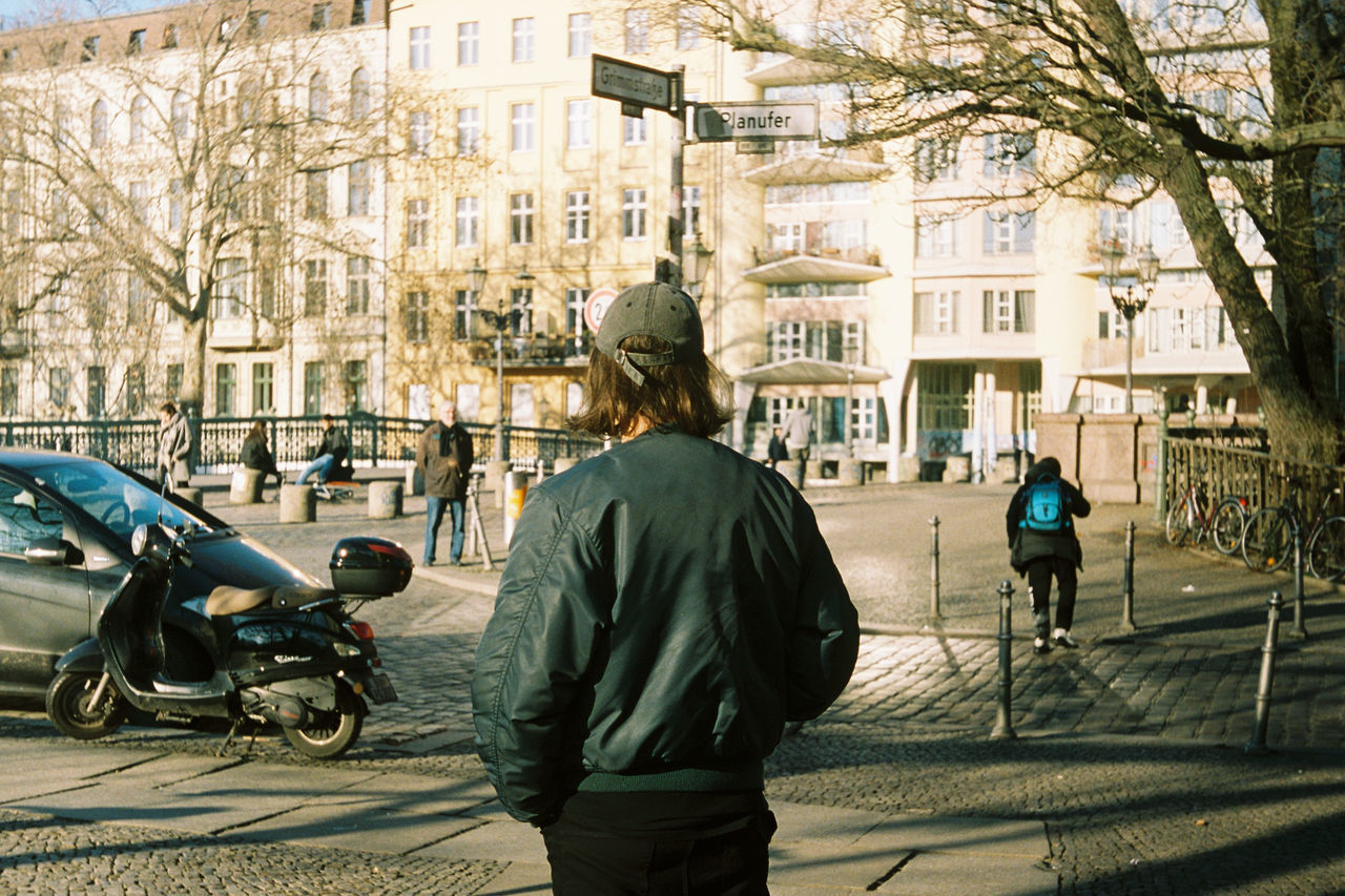 REAR VIEW OF MAN ON STREET IN CITY