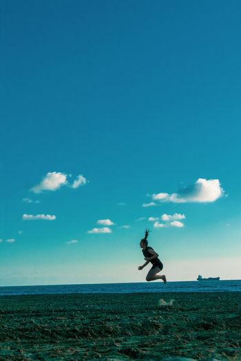 Full length of woman jumping on beach against sky