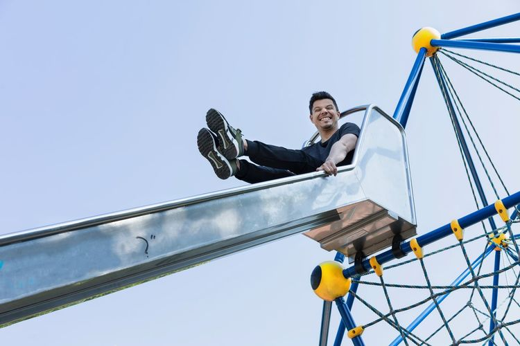 Low angle view of man sitting on slide against blue sky