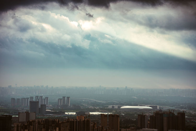 Aerial view of buildings in city against storm clouds