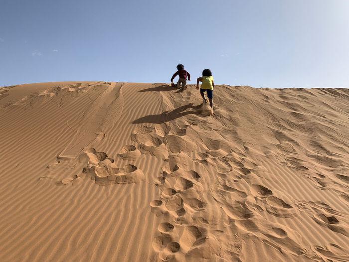 Kids walking on sand dune in desert against sky