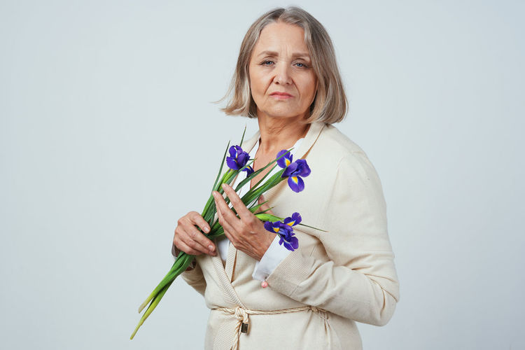 Happy woman with arms raised standing against white background