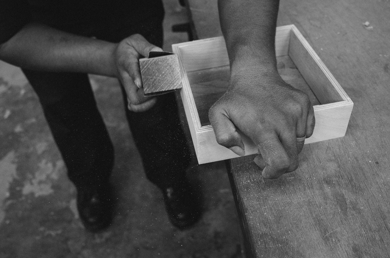 Cropped image of carpenter shaving wood in workshop