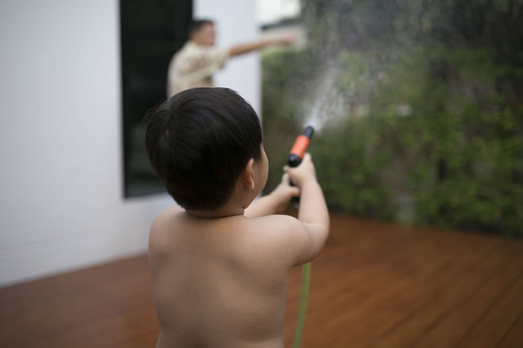 Rear view of shirtless boy spraying water at backyard